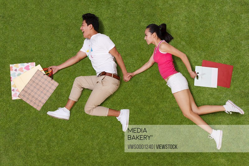 Young couple holding shopping bags on grass