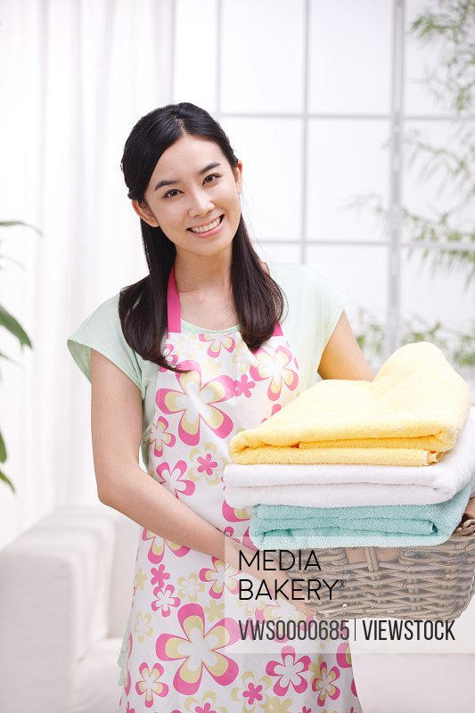 Young woman holding basket of towels