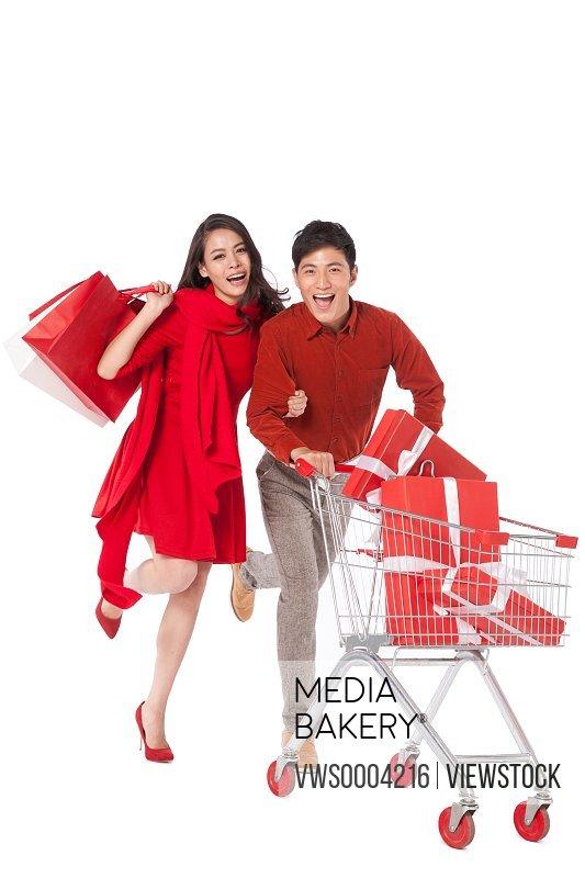 Young couple pushing a shopping cart
