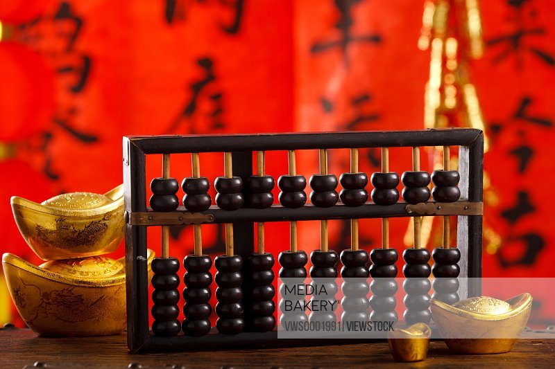 Close-up of gold ingots and abacus