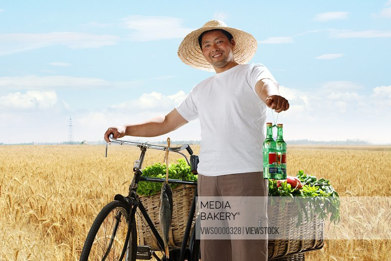 Farmer holding wines with bicycle and vegetable