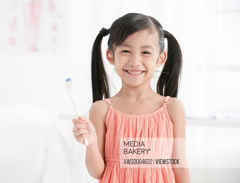 Oriental child holding a toothbrush