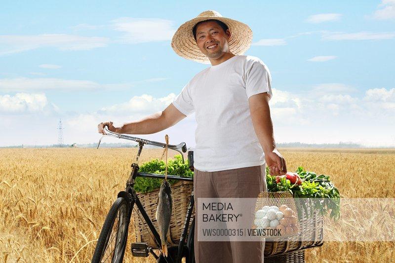 Farmer walking bike with vegetable and eggs