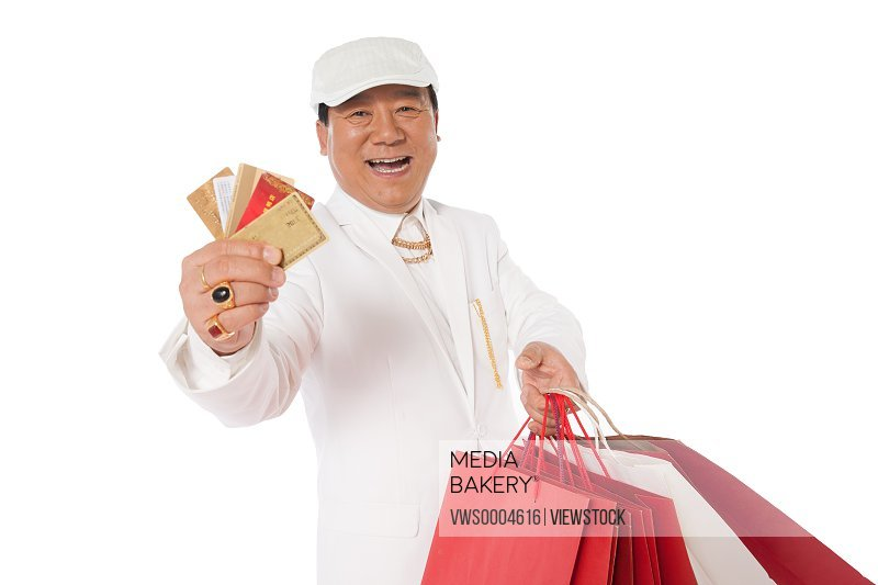 Successful man holding a shopping card