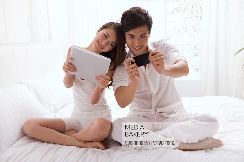 Young couple holding mobile phone and tablet computor on bed