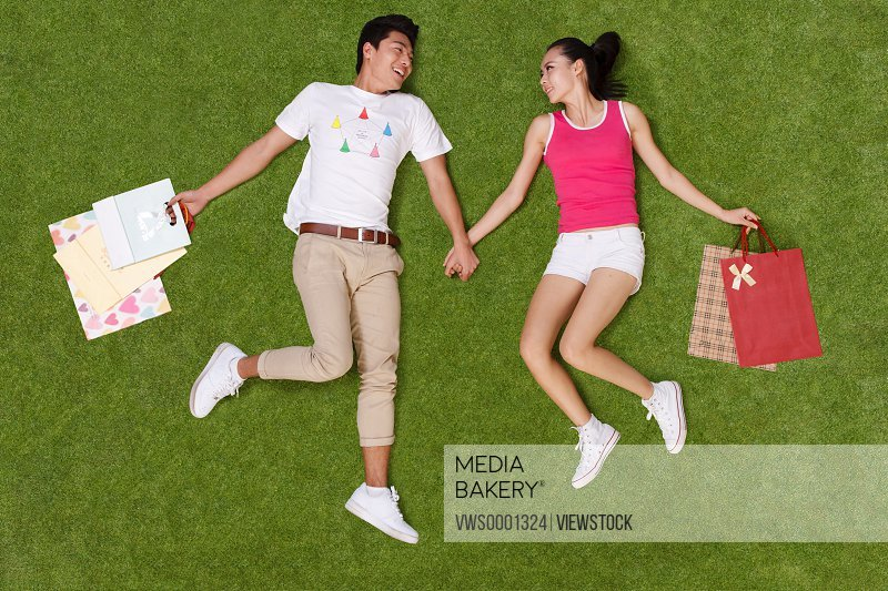 Young couple holding shopping bags lying on grass