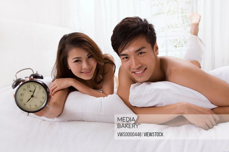 Young couple holding alarm clock on bed