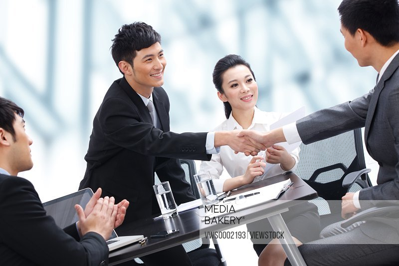 Businesspeople shaking hands at meeting