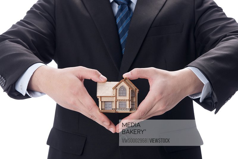 Businessman holding house model