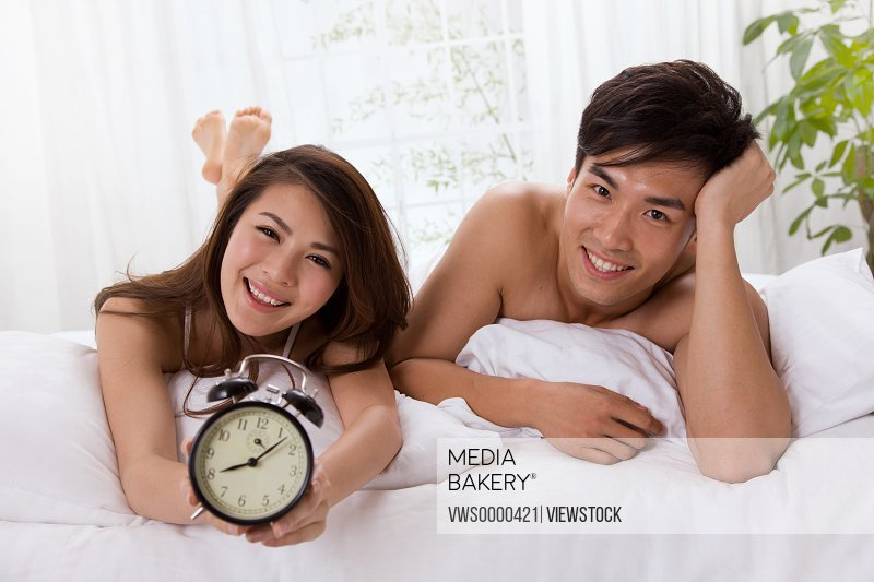 Young couple holding alarm clock lying on bed