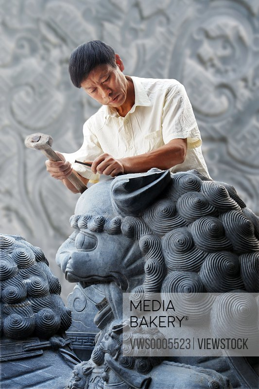 man carving on stone
