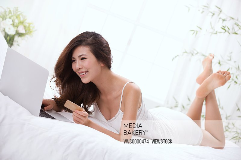 Young lady holding credit card and laptop on bed