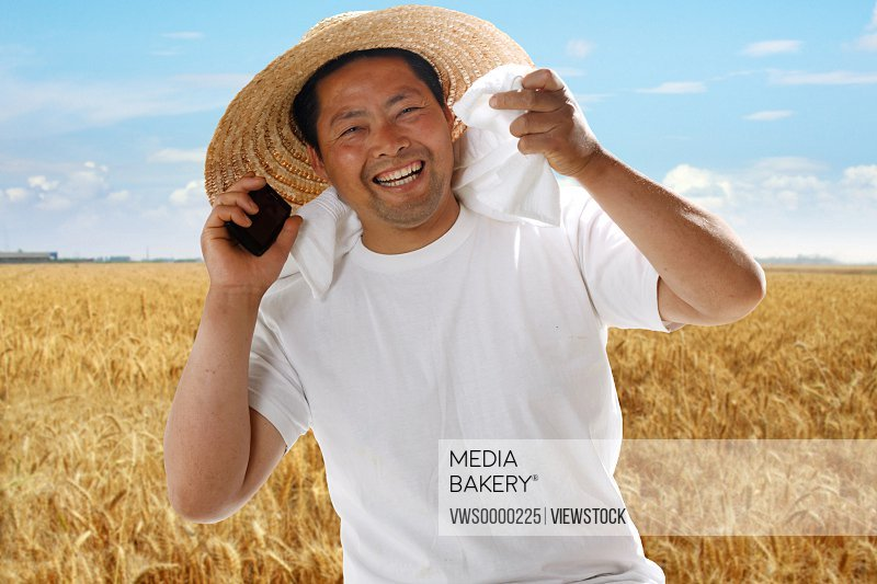 Farmer making phone call in wheat field
