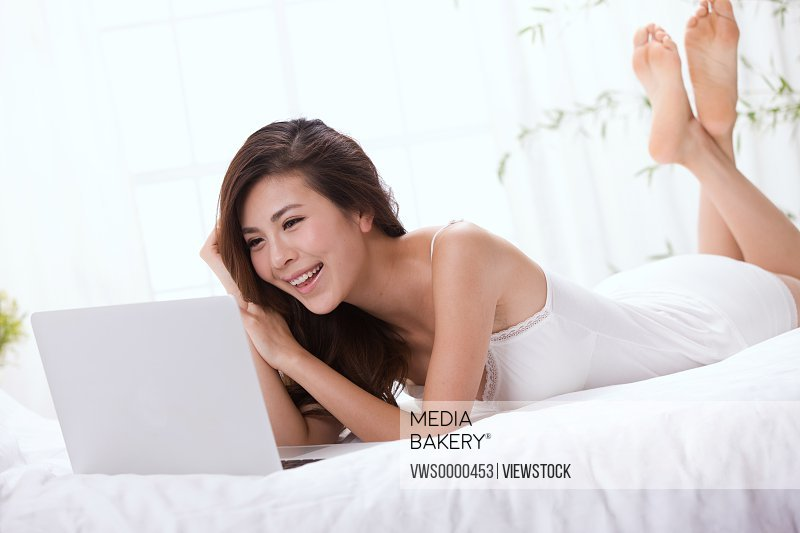 Young lady using laptop on bed