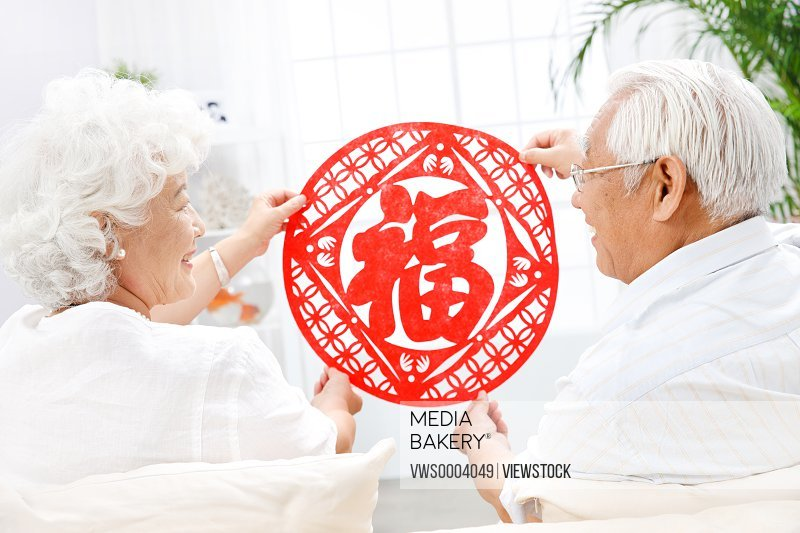 Old couple paste a Fu character