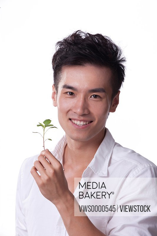 Young man holding seedling