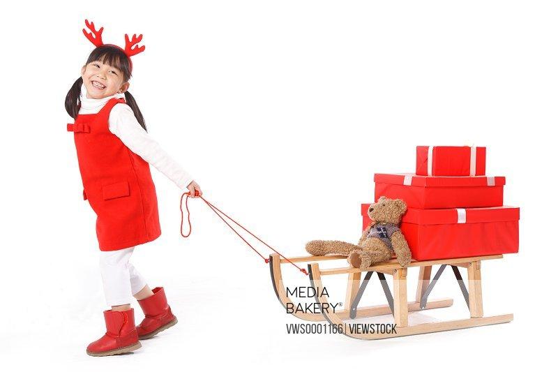 Girl pulling Christmas gift on sled