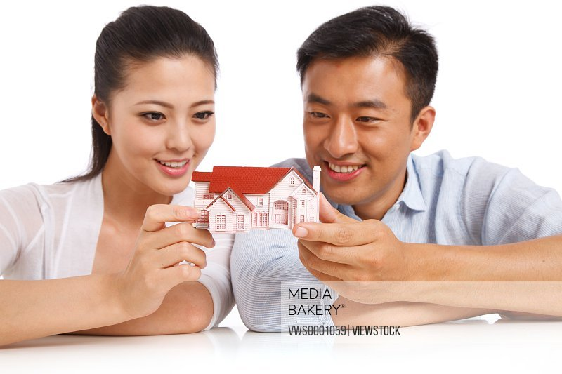 Young couple holding house model