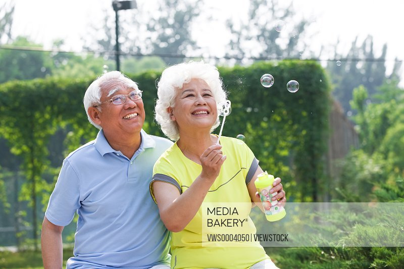 Old couple blowing bubbles