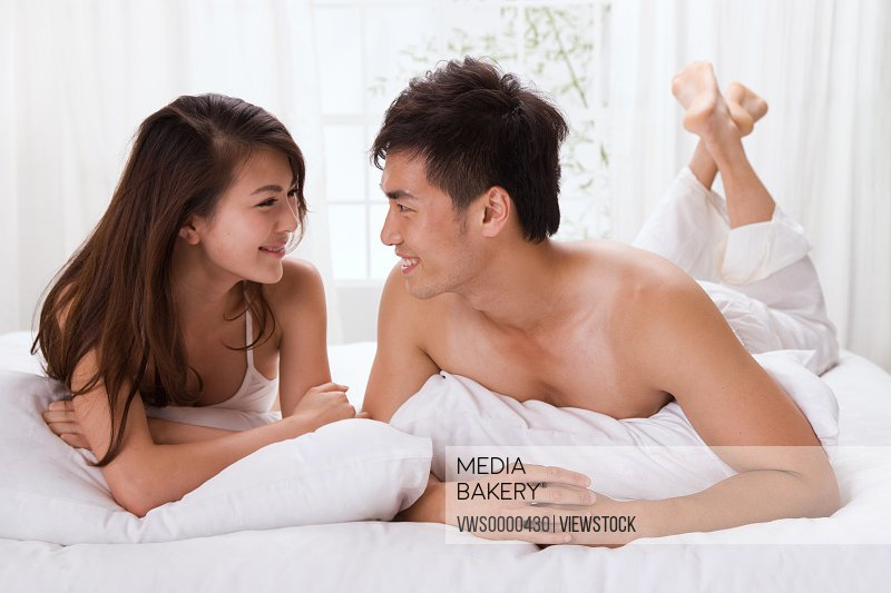 Young couple lying on bed face to face