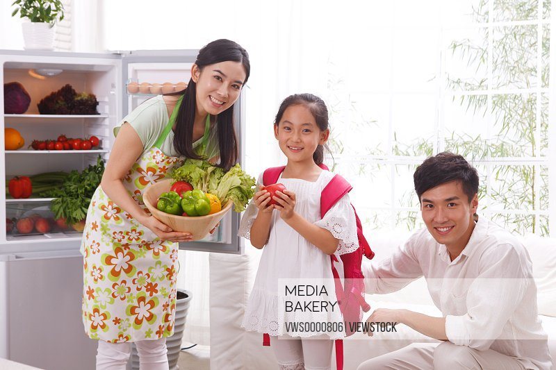 Family holding vegetables in kitchen