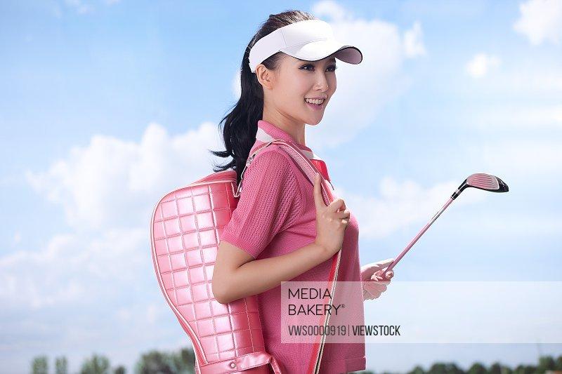 Woman carrying golf bag