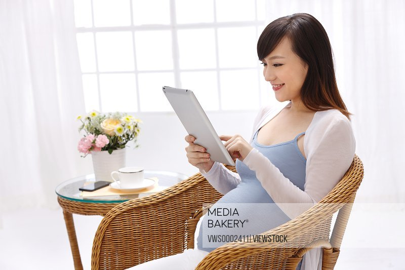 Pregnant woman watching the tablet