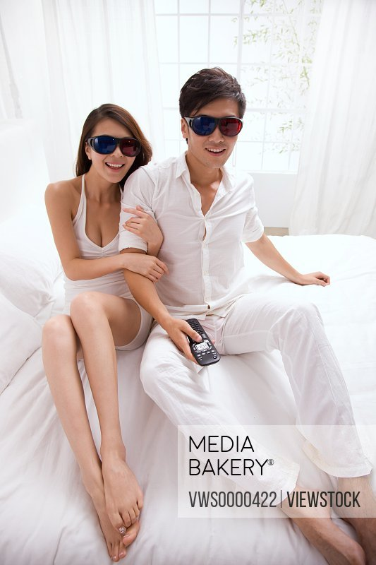 Young couple watch 3D tv on bed