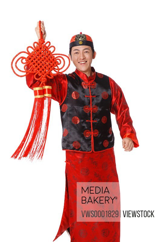 Young man dressed in Chinese traditional clothes holding Chinese knot
