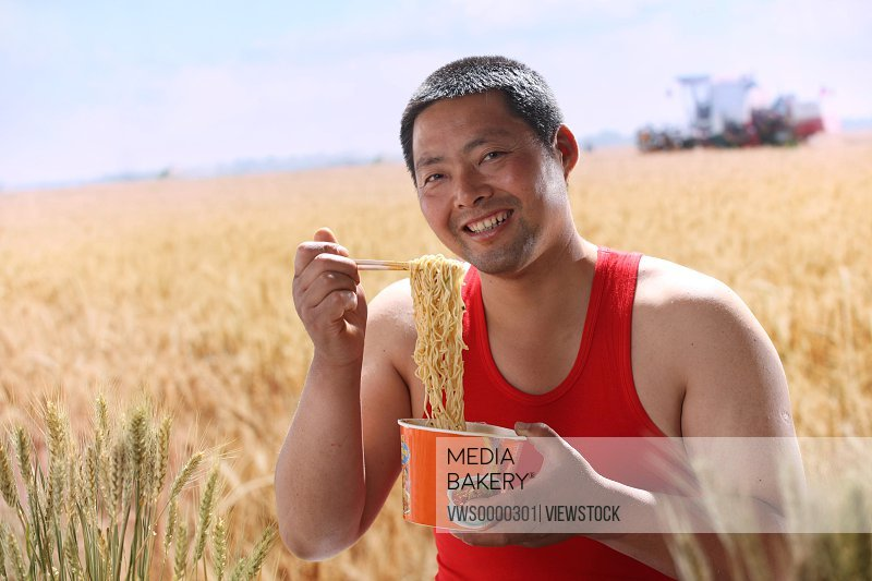 Farmer eating instant noodle in field