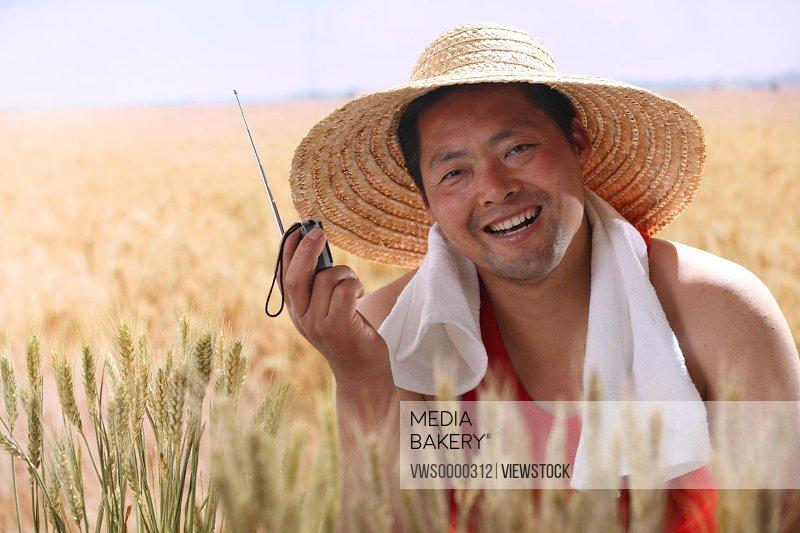 Farmer listening to radio in wheat field