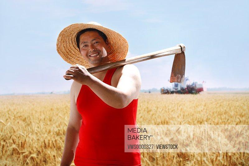 Farmer holding hoe on shoulder