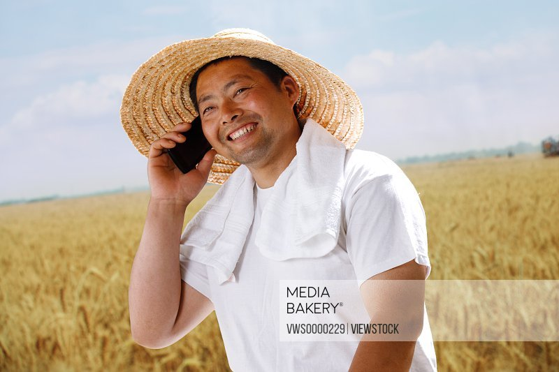 Farmer making phone call in wheat field