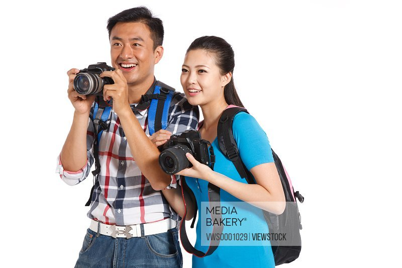 Young couple travelling and carrying camera