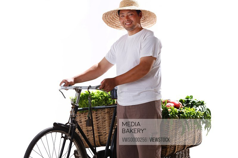 Farmer standing by bicycle with vegetables