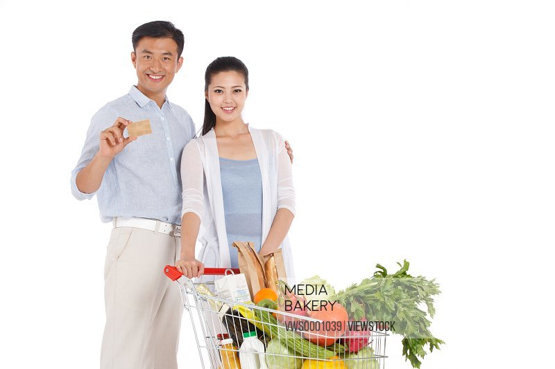 Young couple holding credit cart with vegetable