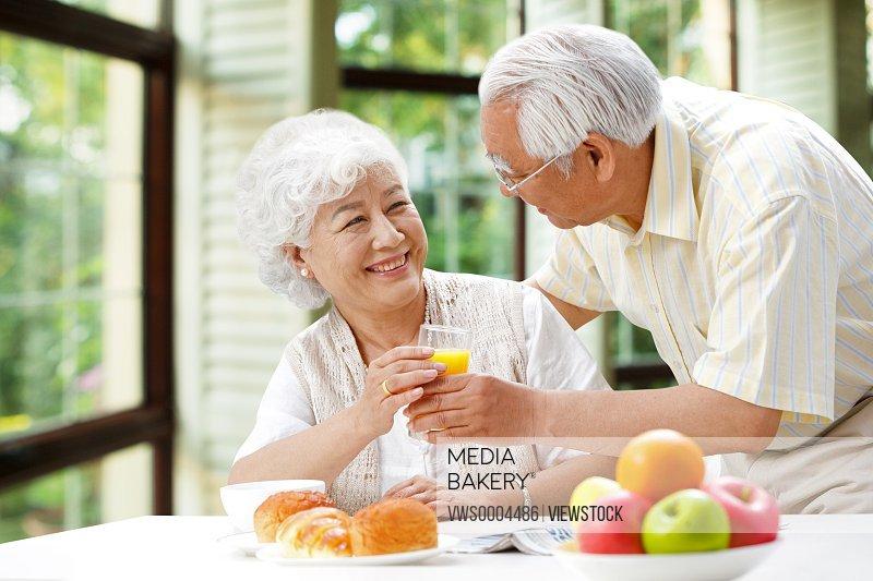 Happy elderly couple drinking juice