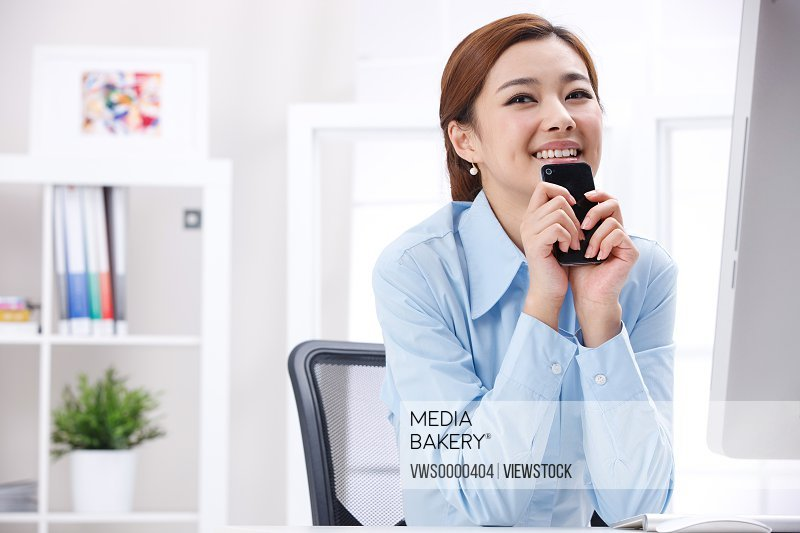 Young business lady holding cellphone