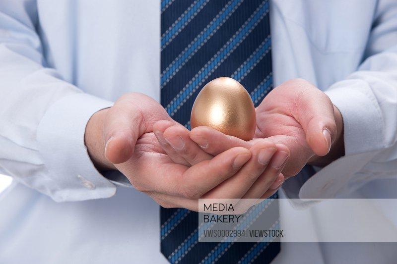 Businessman holding gold egg