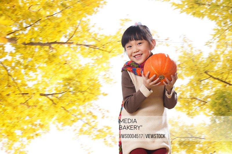 A oriental girl holding a pumpkin