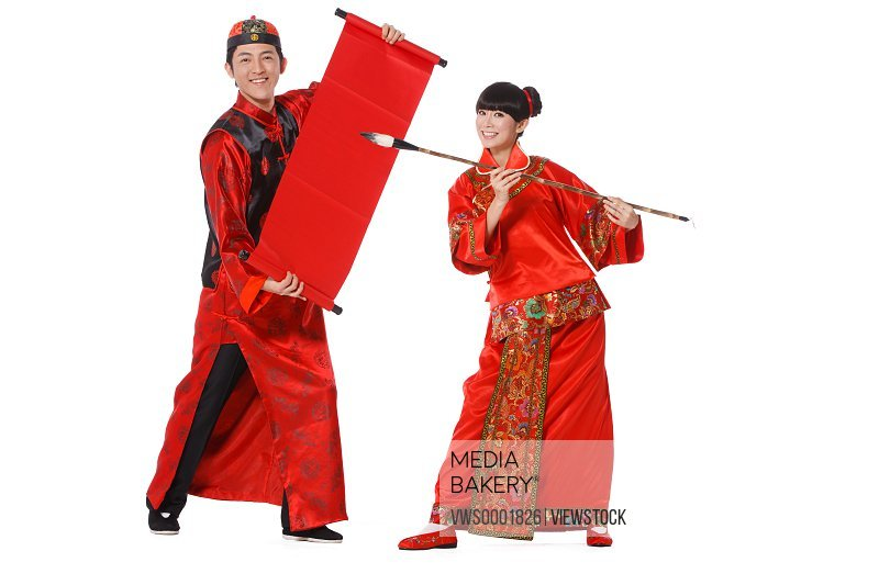 Young couple dressed in traditional clothes dancing celebrating Chinese New Year