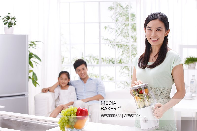 Young woman holding blender with family in kitchen
