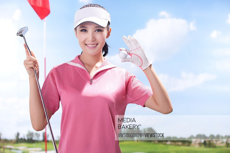 Young woman holding golf ball
