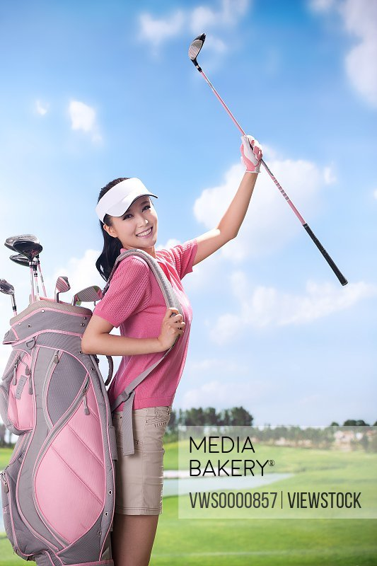 Woman carrying golf bag