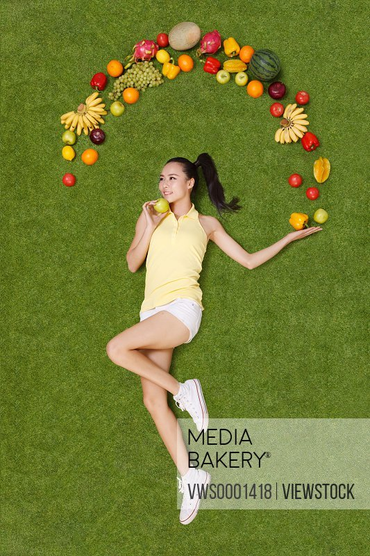 Young woman lying on grass with fruits