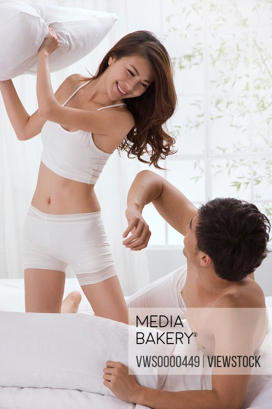 Young couple fighting for fun on bed