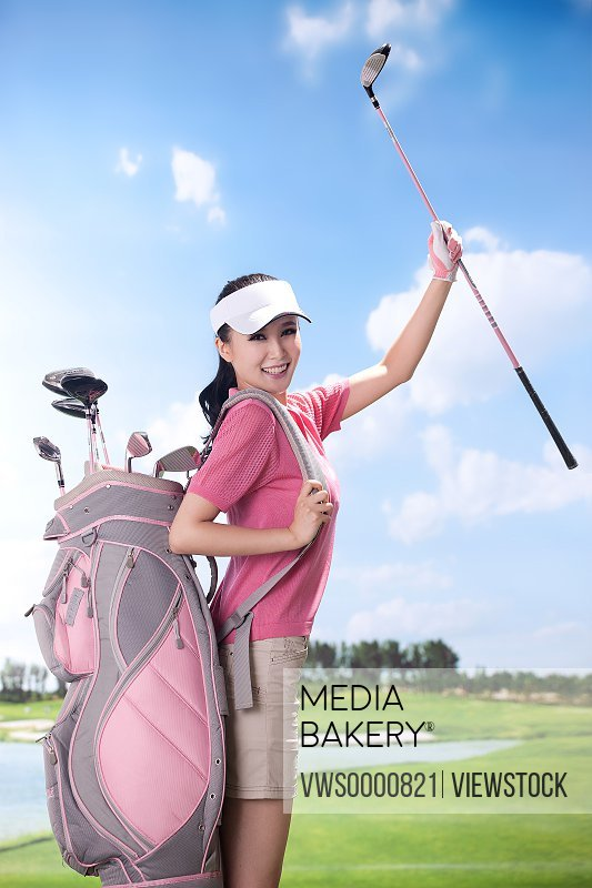 Sexy woman carrying golf bag