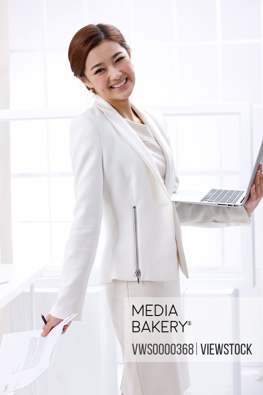 Young business lady holding laptop