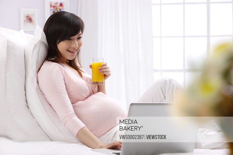 Pregnant woman drinking juice