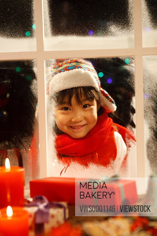 Girl looking at Christmas gift through window